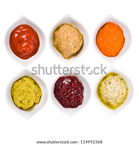 Six different sauces in a white bowl with spoons different colors on the horizontal surface isolated on white background - stock photo