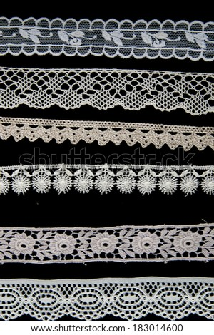 Six different white lace patterns on black background - stock photo