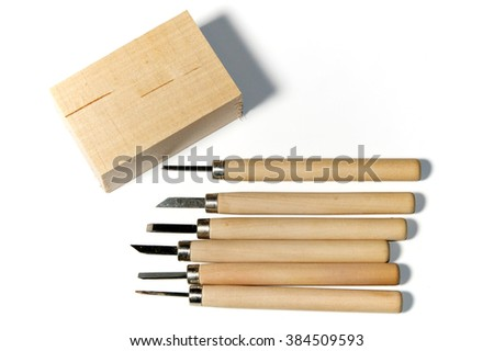 Six different wood carving tools and a block of basswood, over white, not isolated