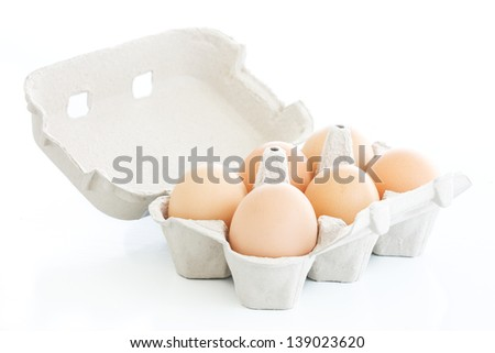 Six eggs on a carton box over a white background - stock photo