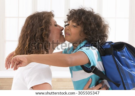 six-eight years old boy and his mother with backpack