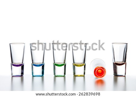Six empty colorful glass shots in a row