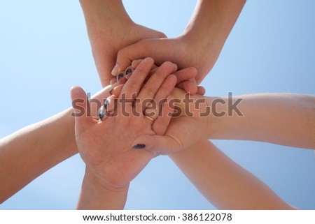 Six female hands connected against the sky.