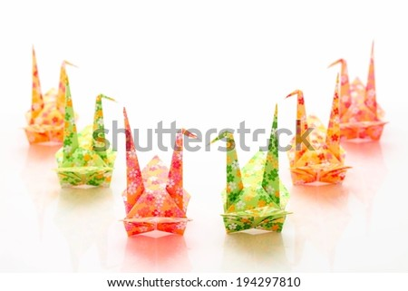 Six folded origami cranes made with brightly colored paper. - stock photo