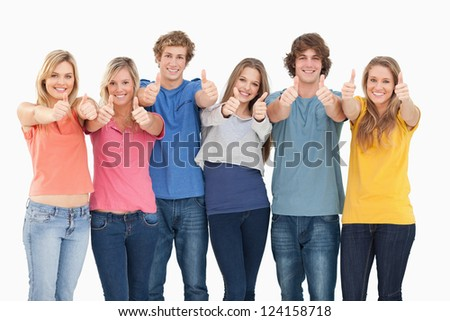 Six friends looking at the camera while smiling as they give a thumbs up - stock photo