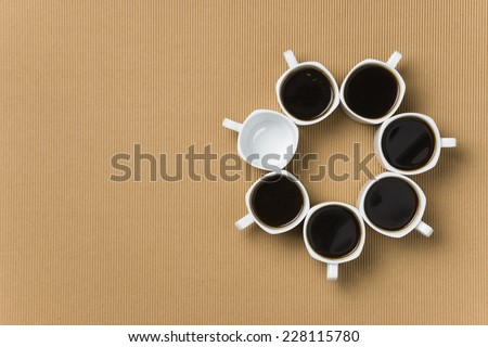Six full and one empty white porcelain coffee cups making a circle - stock photo