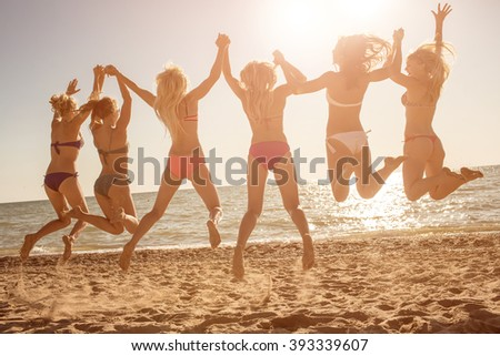Six girls  jumping on beach at sunset.