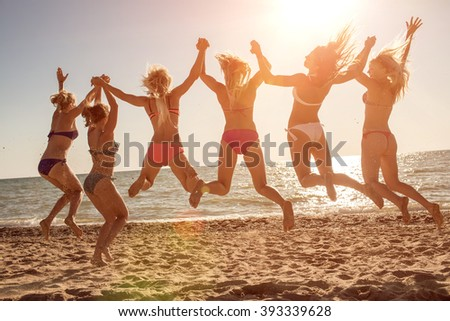 Six girls  jumping on beach at sunset. - stock photo