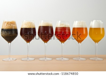 Six glasses with different beers on wooden table - stock photo
