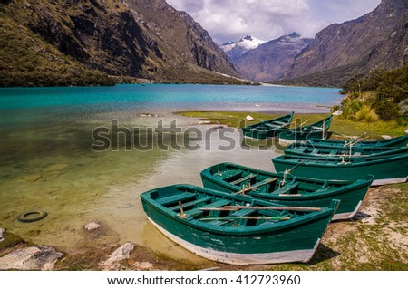 Six green boats are waiting to be sailed across the blue glacier lagoon in the Peruvian Andes. Huaraz is a popular tourist destination for alpine hiking. - stock photo