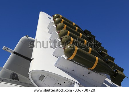 Six green bombs mounted onto the folded wing of a military fighter jet.  - stock photo