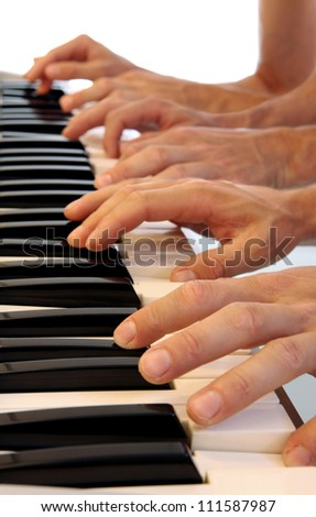 Six hands playing simultaneously on a grand piano with bright white background