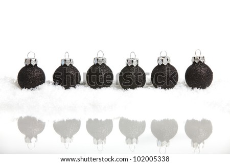 Six little black christmas tree balls in the snow mirrored, on white background - stock photo