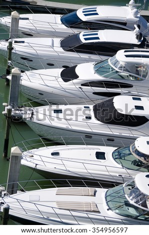 Six luxury yachts lined up at a marina dock.