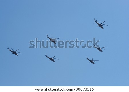 Six military helicopters against the blue sky - stock photo