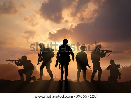 Six military silhouettes on sunset sky background - stock photo