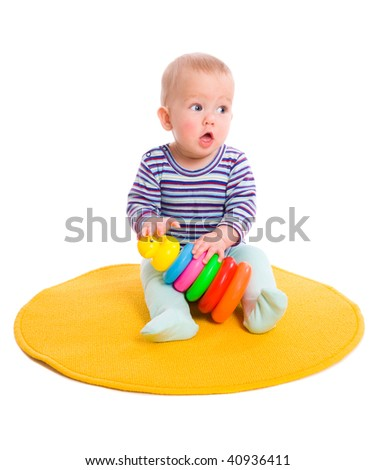 Six month Baby playing with pyramid isolated on white - stock photo