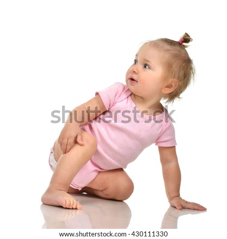 Six month infant child baby toddler sitting in pink body and diaper looking at the corner isolated on a white background - stock photo