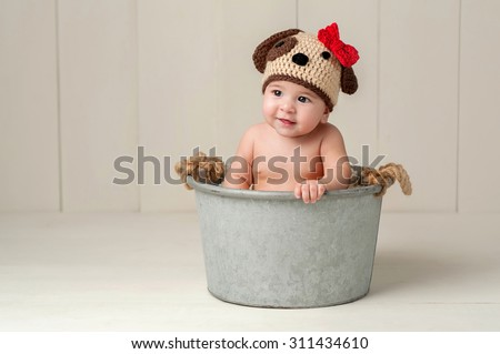 Six Month Old Baby Girl Wearing a Crocheted Puppy Dog Hat. Shot in the Studio on a White Wooden Floor and Backdrop. - stock photo