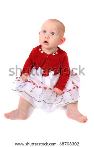 Six month old baby girl with big blue eyes and red velvet jacket looking up on a white background (not isolated)