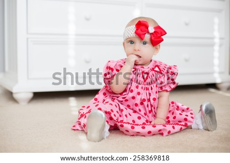 Six month old baby sits in red Valentine's day dress - stock photo