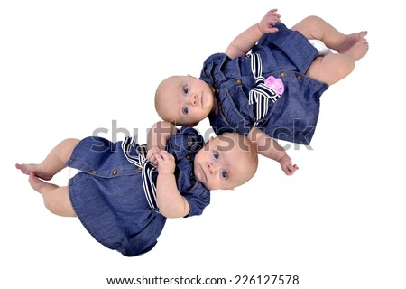 Six month twin sisters on white background, lying top-to-tail - stock photo