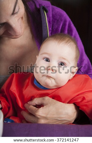 six months age blonde caucasian baby red bib in woman mother purple velvet jacket arms eating puree