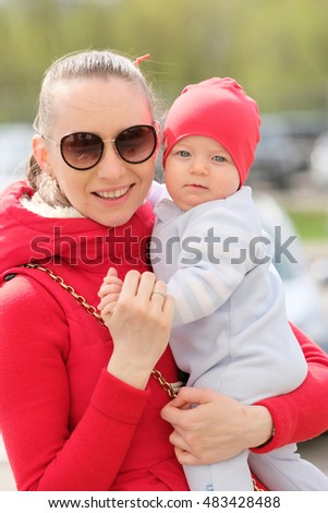 Six months old baby boy with his mother outdoors