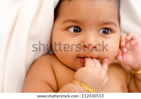 Six months old Indian baby girl sucking her fingers