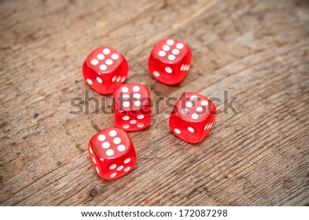 Six numbers on faces of five red dices on wooden floor - stock photo