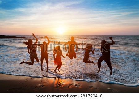 Six people with a shadow cast on them are jumping on beach at sunset. - stock photo