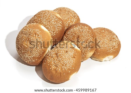 Six piled freshly baked golden hamburger rolls sprinkled with sesame seeds on white background