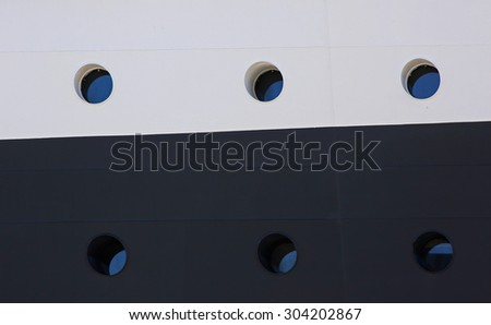 Six portholes on a multi-colored side of a cruise ship.