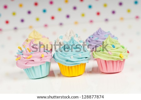 six rainbow cupcakes on a dotted background