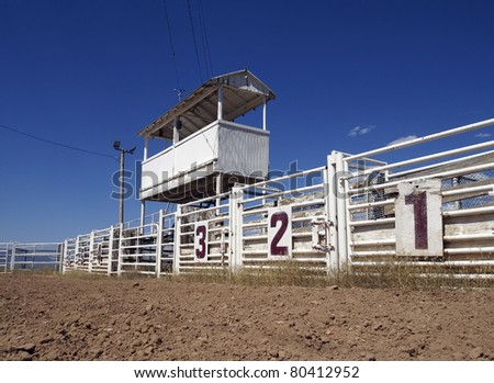 Six rodeo gates beneath the announcer's booth at a rural rodeo. - stock photo