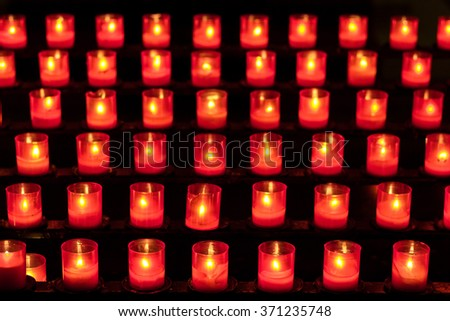 Six rows of candles in red glasses on a rack