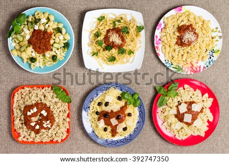 Six square and circular plates filled with various types of pasta topped with herbs, marinara sauce, cheese and other delicious ingredients - stock photo