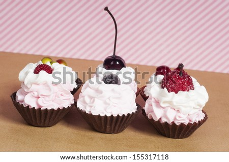 Six strawberry cupcakes with pink whipped cream and fruit on top - stock photo