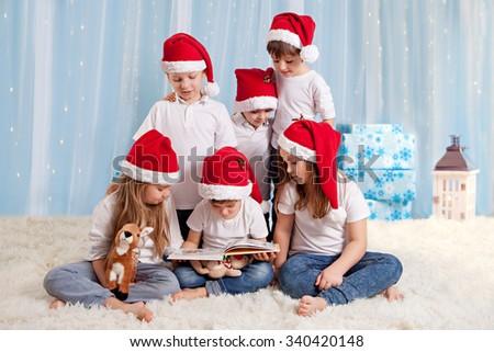 Six sweet kids, preschool children, having fun for christmas, reading a book studio shot - stock photo