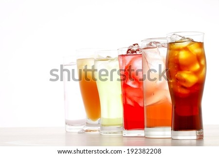 Six tall glasses full of assorted beverages and ice. - stock photo
