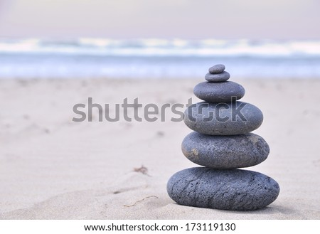 Six volcanic stones stacked on the beach.