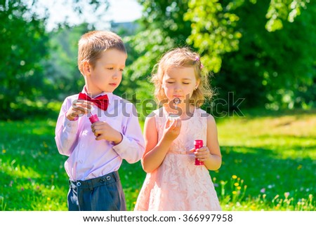 six year old boy looks at the girl makes soap bubbles - stock photo
