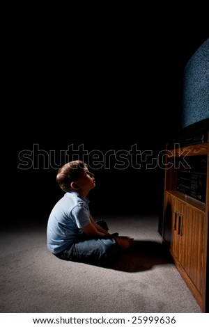 Six year old boy watching static on television in the dark - stock photo
