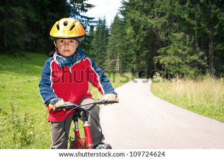 Six year old kid outdoor on bike. Bicycle path from St. Candid in italy to Lienz in Austria. - stock photo