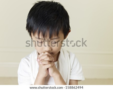 six year old little asian boy praying. - stock photo