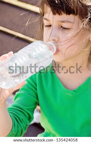 six year old little girl drinking from a bottle of water. She is outdoors and the wind is blowing her hair. She is half caucasian and half Vietnamese ethnicity. - stock photo
