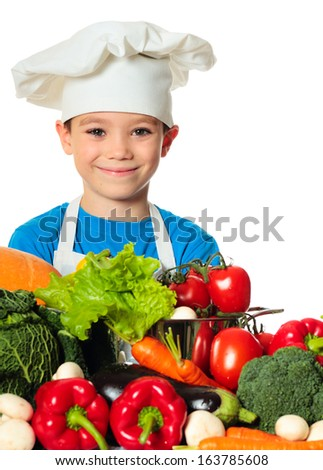 Six years old cook boy with different vegetables isolated on white - stock photo
