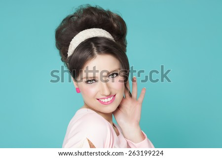 Sixties fashion woman with retro hairstyle and makeup smiling over cyan blue background. - stock photo
