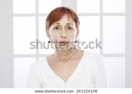 Sixty years old woman face - stock photo