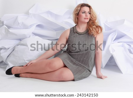 Size Full length portrait of a beautiful plus curly young blond woman posing on white in gray dress and pumps / Portrait of a beautiful plus size curly young blond woman - stock photo